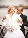 Mid-aged bald groom hugging bride from back Royalty Free Stock Photo