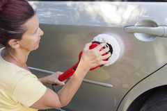 Mid aged cute woman polishing her car Stock Photos