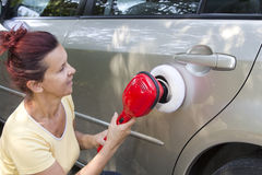 Mid aged cute woman polishing her car Stock Image