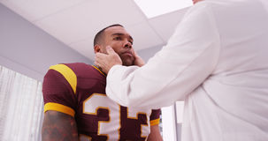 Mid aged doctor checking football player's sports neck injury Royalty Free Stock Image