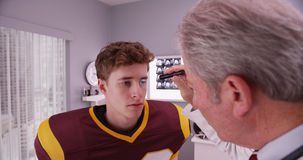 Mid-aged doctor examining football player after concussion.  Stock Images