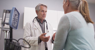 Mid-aged doctor talking to female patient Stock Photos