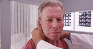Mid aged male patient having neck examined by medical physician Stock Photos