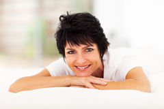 Mid aged woman. Pretty mid aged woman lying on bed at home Royalty Free Stock Images