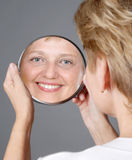 Mid aged woman. Looking on mirror Royalty Free Stock Image