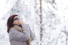 Mid aged woman blowing nose. Portrait of a cute mid aged woman blowing nose-sneezing, outdoors on winter day Stock Photos