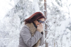 Mid aged woman blowing nose. Portrait of a cute mid aged woman blowing nose-sneezing, outdoors on winter day Stock Photo