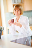 Mid aged woman with a cup of coffee in the kitchen Stock Images