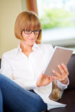 Mid aged woman at home with pad Royalty Free Stock Photography
