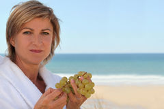 Mid aged woman near the sea. Mid aged woman eating grapes near the sea Stock Photography
