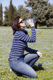 Mid aged woman relaxing and drinking water on grass Royalty Free Stock Image
