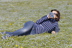 Mid aged woman relaxing and drinking water on grass Royalty Free Stock Images
