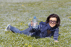 Mid aged woman relaxing and drinking water on grass Stock Image