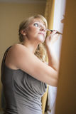 Mid-Aged Woman Self Applying Facial Makeup Indoors Royalty Free Stock Photo