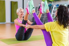 Mid-aged woman working out in pairs on mats in a gym. in sportswear doing yoga buddy boat pose with partner. Mid-aged women working out in pairs on mats in a gym stock photo
