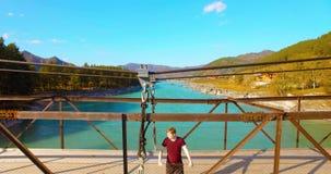 Mid-air πτήση πέρα από την παραμονή τουριστών νεαρών άνδρων πέρα από μια γέφυρα αναστολής απόθεμα βίντεο