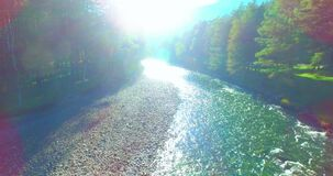 Mid air flight over fresh and clean mountain river at sunny summer morning. Aerial UHD 4K view. Mid-air flight over fresh and clean mountain river at sunny stock footage