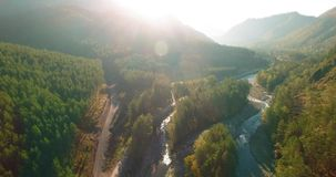Mid air flight over fresh mountain river and meadow at sunny summer morning. Rural dirt road below. stock video footage
