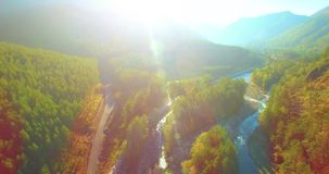 Mid air flight over fresh mountain river and meadow at sunny summer morning. Rural dirt road below. stock video