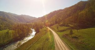 Mid air flight over fresh mountain river and meadow at sunny summer morning. Rural dirt road below. Cows and car. stock footage
