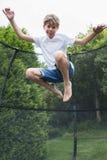 Mid Air ha sparato del ragazzo sul trampolino in giardino immagini stock