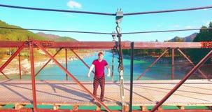 Mid-air vlucht over jonge mensentoerist het blijven over een hangbrug stock videobeelden