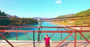 Mid-air vlucht over jonge mensentoerist het blijven over een hangbrug stock footage
