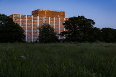 Mid-Century Building at Sunset - Abandoned State Hospital. A view at sunset of an abandoned Mid-Century state hospital building surrounded by tall grasses Royalty Free Stock Photo