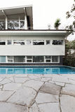 Mid century home exterior with blue tiled swimming pool and crazy paving. Patio royalty free stock photography