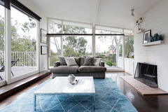 Mid century modern living room with huge windows to view the treetops. Mid century modern living room with huge windows to view the Australian treetops stock images