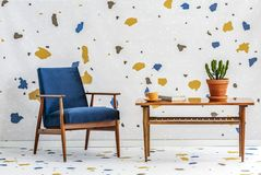 Mid-century modern, navy blue armchair and a retro wooden table in a white living room interior with lastrico pattern on the wall royalty free stock images