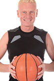 Mid forties basketball player. Mid forties blond male basketball player with ball, studio shot, white background Royalty Free Stock Photos