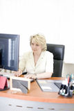 Mid-life business woman. Look at monitor Stock Photography