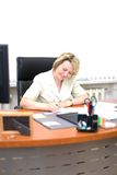 Mid-life business woman write document Stock Image
