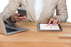 Mid-section της επιχειρηματία που χρησιμοποιούν το κινητό τηλέφωνο και της ψηφιακής ταμπλέτας με το lap-top στον πίνακα Στοκ εικόνα με δικαίωμα ελεύθερης χρήσης