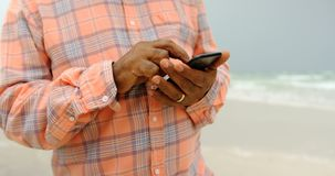 Mid section of active senior African American man using mobile phone on the beach 4k stock video footage