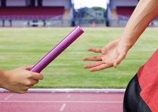 Mid-section of athlete passing the baton to teammate. In stadum royalty free stock image