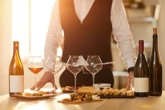 Sommelier. Mid section background of unrecognizable sommelier standing by table with wine bottles and snacks during tasting session lit by sunlight, copy space royalty free stock photography