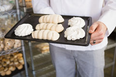 Mid section of baker holding meringue tray Royalty Free Stock Image