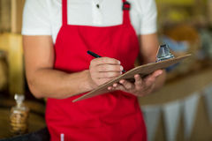 Mid section of bakery staff writing on clipboard at counter Stock Image
