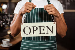 Mid section of barista holding open sign Stock Photo