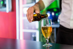 Mid section of bartender pouring beer in a glass Stock Photos