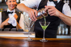 Mid section of bartender pouring cocktail into glasses. Bartender pouring cocktail from shaker into glasses at bar counter in bar stock images