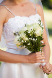 Mid section of a beautiful bride with bouquet in park Stock Photos