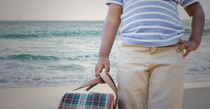 Mid section of boy holding a bag at beach Stock Images