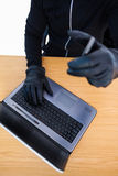 Mid section of a burglar using laptop and smartphone Stock Image