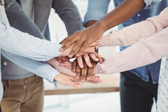 Mid section of business team putting their hands together. At office Stock Photos