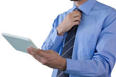 Mid section of businessman adjusting necktie while holding tablet Royalty Free Stock Images