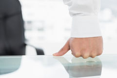 Mid section of a businessman with clenched fist on desk Royalty Free Stock Photos