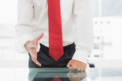 Mid section of a businessman with clenched fist on desk Stock Photos